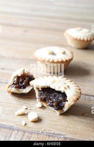 Selection of several mince pies, some broken open or partly eaten. A traditional festive Christmas dessert or pudding. - Stock Photo
