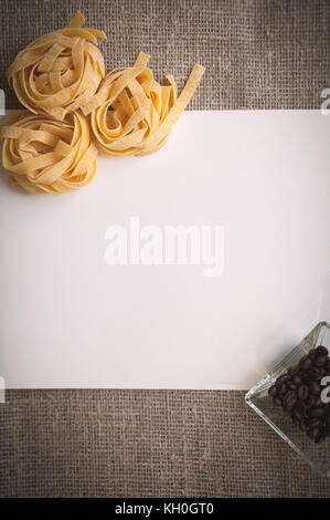 Raw fettuccine pasta and coffee beans in bowl on linen fabric - Stock Photo