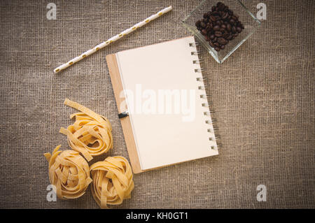 notebook, raw fettuccine pasta and coffee beans in bowl - Stock Photo