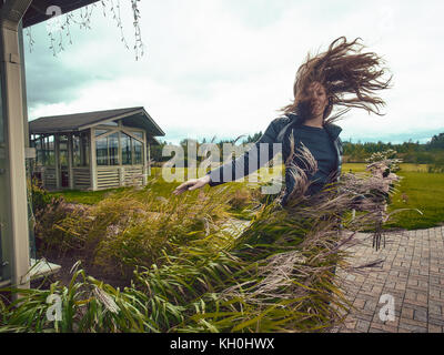 A young red-haired girl corrects her long hair flying from a gust of wind.The girl wears a blue jacket and jeans. - Stock Photo