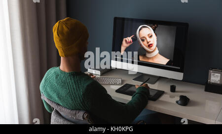 Man working at home editing pictures on computer - Stock Photo