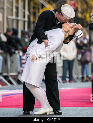 New York, USA, 11 Nov 2017.  A man dressed as a sailor pretends to kiss a woman dressed in white during the 2017 - Stock Photo