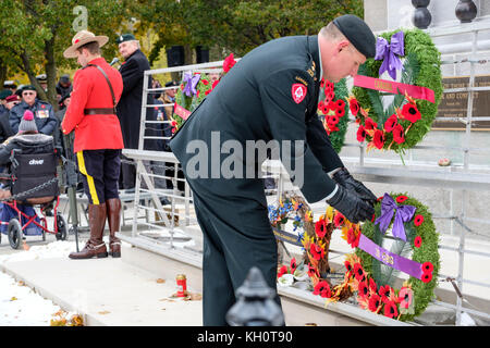 Royal Canadian Regiment (RCR) officer lays a poppy wreath at the downtown cenotaph during Remembrance Day ceremony - Stock Photo