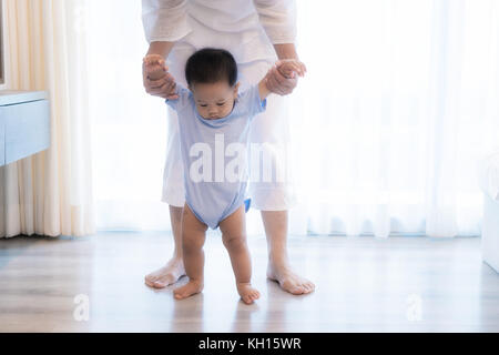 Happy Asian little baby boy learning to walk with mother help in bedroom at home. Family, child, childhood and parenthood - Stock Photo