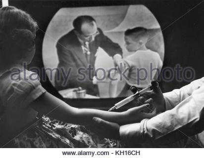 An eight-year-old girl receiving her own polio vaccine watches Dr. Jonas Salk inoculate a boy on closed circuit - Stock Photo