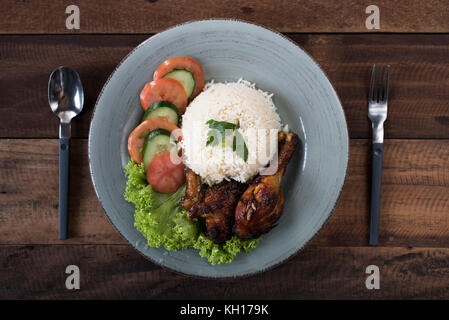 Popular Malaysian dish Nasi Ayam or chicken rice with baked chicken pieces, tomato, cucumber and salad. - Stock Photo