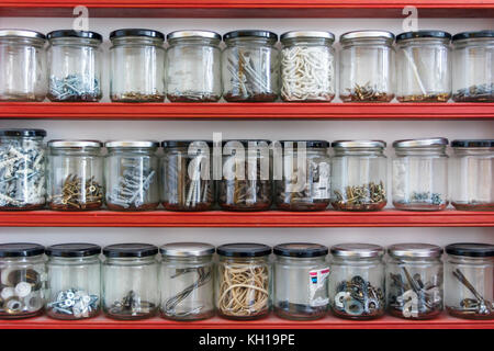 Miscellaneous hardware components stored in glass jam jars on three shelves in a home workshop - Stock Photo