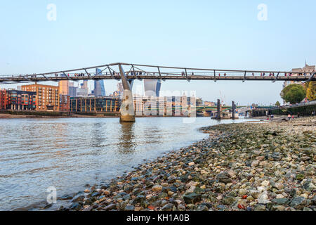 The Millennium Bridge, London, UK, seen from the Thames foreshore at Bankside, at low tide on an autumn evening - Stock Photo