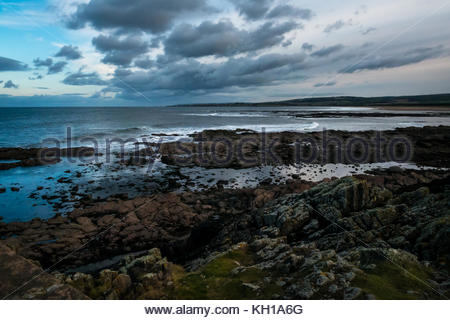 Rocky shore, St Baldred's Cradle, Ravensheugh Sands, East Lothian, with dramatic sky looking to Belhaven Bay with - Stock Photo