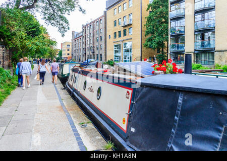 People walking away on the towpath of Regent's Canal past narrowboats moored at Battlebridge Basin, King's Cross, - Stock Photo