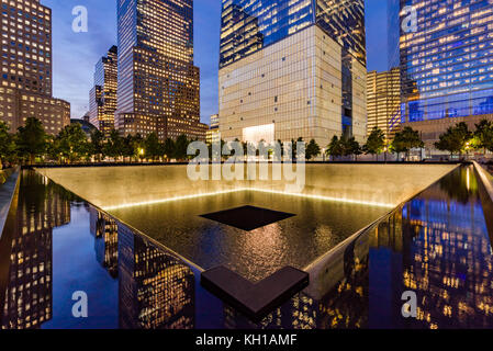The North Reflecting Pool illuminated at twilight with view of One World Trade Center. Lower Manhattan, 9/11 Memorial - Stock Photo