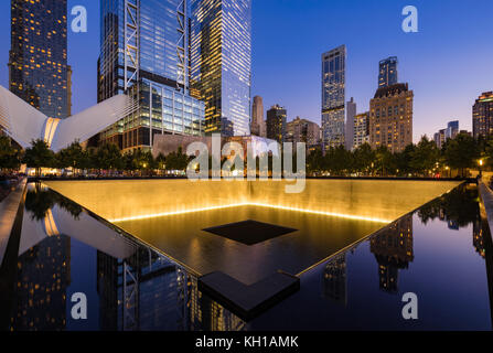 The North Reflecting Pool illuminated at twilight with view of the World Trade Center Tower 3 and 4 and the Oculus. - Stock Photo