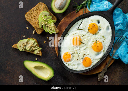 Scrambled eggs on a cast iron skillet and avocado sandwich with fresh sliced avocado and pine nuts on a dark slate - Stock Photo