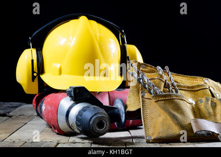 Safety accessories and impact hammer. Accessories for a builder on a wooden table. Black background. - Stock Photo