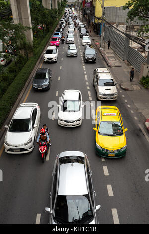 Typical rush hour view from a over head walkway of morning 3 lane traffic in Bangkok, Thailand. - Stock Photo