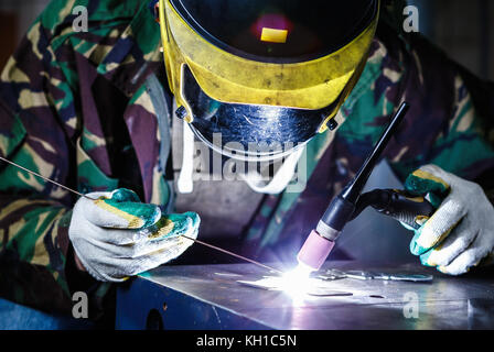 Professional welder in mask welds steel with electric welding torch tool.Factory worker welding metal parts with - Stock Photo