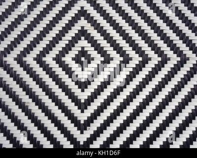 A black and white diamond pattern formed in woven plastic as a background - Stock Photo