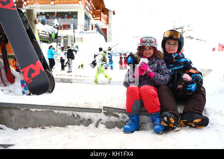 kids in the snow wearing ski suits, helmets and goggles - Stock Photo