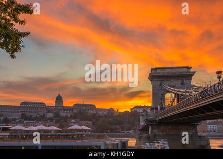 Budapest, Hungary - Beautiful dramatic golden sunset at Szechenyi Chain Bridge with Buda Castle Royal Palace at - Stock Photo