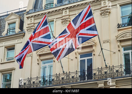 Two flags of Great Britain, commonly called Union Jacks, fly from a building in central London. - Stock Photo