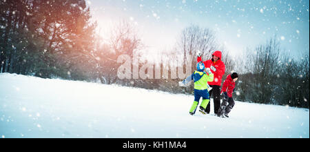 Father with sons walking at snowfall - Stock Photo