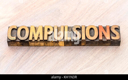 compulsions - word abstract in vintage letterpress wood type printing blocks - Stock Photo