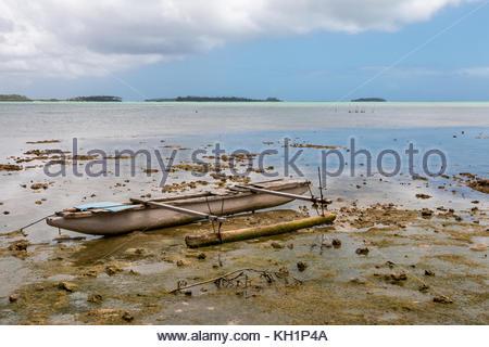 Abandoned old outrigger canoe on shallow water, Tongatapu Island, Tonga - Stock Photo