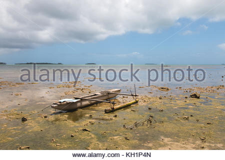 Abandoned old outrigger canoe on shallow water, Tongatapu Island, Tonga - Stock Photo