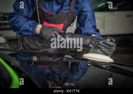 Close-up of a male mechanic with a blue prism and protective gloves polishes a black metal bumper machine with a - Stock Photo