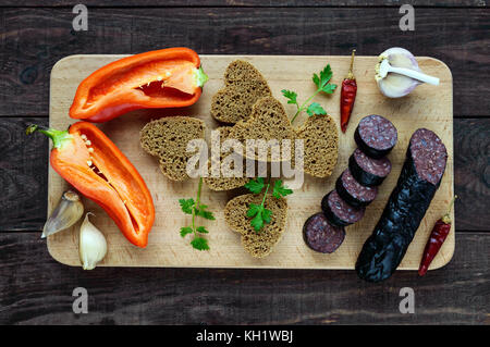 Morcillo (Spanish black pudding, blood sausage), cutting slices, black rye bread in a heart shape, pepper, garlic - Stock Photo