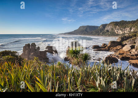 The incoming tide pounding on the rocky shoreline at Punakaiki, in the Paparoa National Park on the West Coast of - Stock Photo