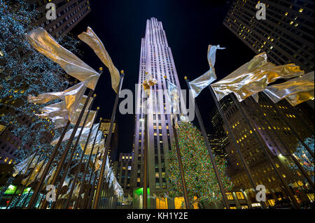 NEW YORK CITY - DECEMBER 21, 2016: Holiday flags fly around the central plaza in front of the Rockefeller Center Christmas Tree, one of the city's top
