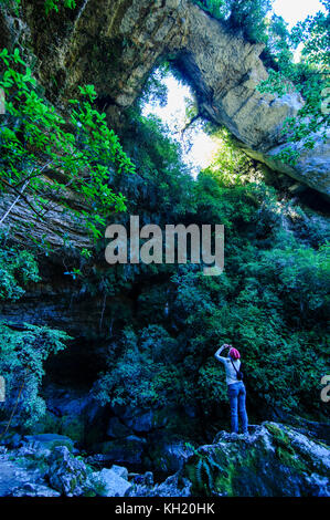 Woman looking at the stunning Oparara arch in the Oparara Basin, Karamea, South island, New Zealand - Stock Photo