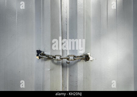 Metal chain securely locking door in an industrial setting - Stock Photo