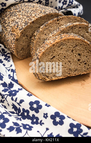 Whole wheat sliced bread closeup , on wooden surface with floral kitchen towel. - Stock Photo