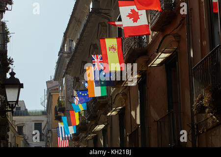 Flags of various world countries are hung out on one of the buildings in Italy and are illuminated by the backlight - Stock Photo