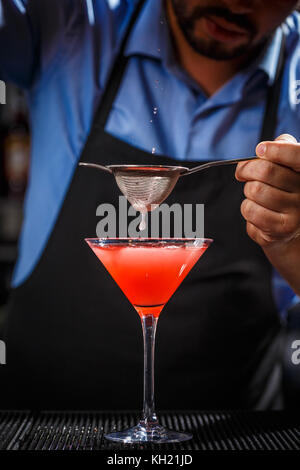Barman is preparing and pouring a red cocktail into martini glass, he makes cosmopolitan cocktail - Stock Photo