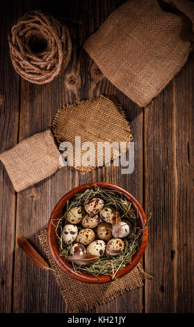 Top view of quail eggs in bowl on wooden background - Stock Photo