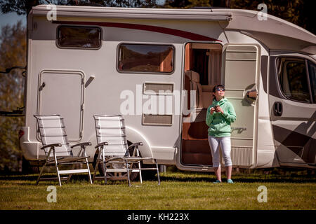 Woman is standing with a mug of coffee near the camper. Caravan car Vacation. Family vacation travel, holiday trip - Stock Photo