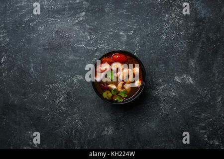 Spicy Thai soup Tom Yam with seafoodon on a vintage colored background. Top view. - Stock Photo