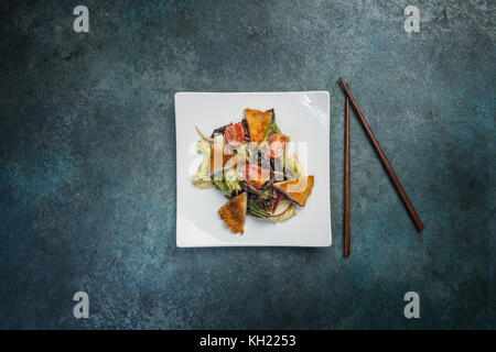 Pan-Asian salad, vegetables with fried chicken. On a square white plate with chopsticks. Top view. - Stock Photo
