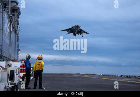 An AV-8B Harrier II jet, attached to Marine Medium Tiltrotor Squadron 162, prepares to land on the flight deck of - Stock Photo