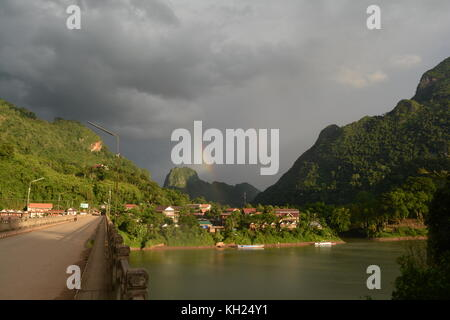 Rainbows above Nong Khiaw, Laos, in the early evening light - Stock Photo