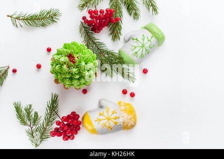 Two cakes in the form of mittens made of marzipan, Christmas tree made of cream lying on the green branches of Christmas - Stock Photo