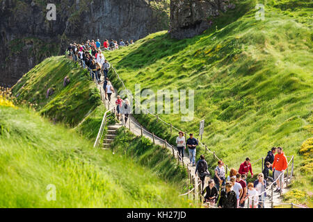 Thousands of tourists visiting Carrick-a-Rede Rope Bridge in County Antrim of Northern Ireland, hanging 30m above - Stock Photo