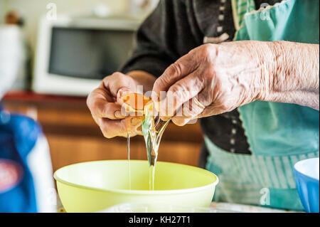 hands of italian grandma holding egg while making pasta - Stock Photo