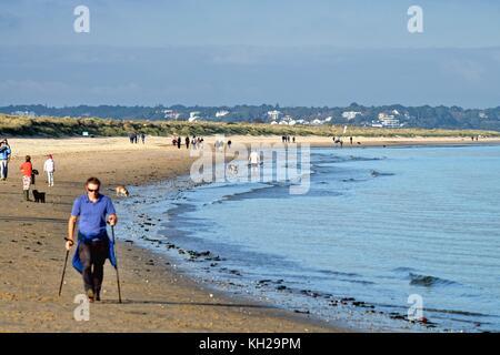 People walking on Studland Bay beach in autumn sun Dorset England uk - Stock Photo