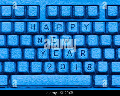 illuminated with blue light computer keyboard with inscription happy new year 2018 covered with snow - Stock Photo