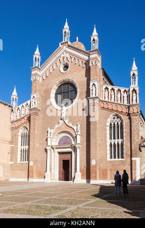 Two tourists standing admiriong the Gothic facade of the church of Madonna dell Orto , Cannaregio, Venice, Italy - Stock Photo