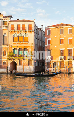 Gondola on the Grand Canal at sunset, Cannaregio, Venice, Italy rowing tourists past Palazzo Bollani Erizzo in golden - Stock Photo
